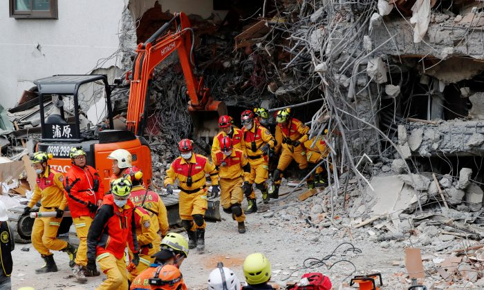 Rescuers run out of a hotel during an aftershock after an earthquake hit Hualien, Taiwan Feb. 7, 2018. (Reuters/Tyrone Siu)