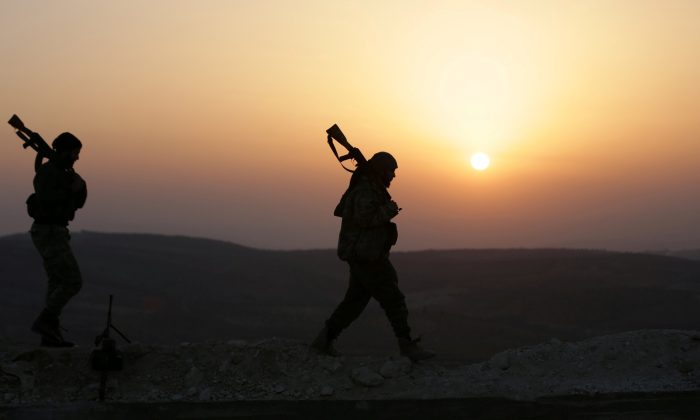 Turkish-backed Free Syrian Army fighters walk as the sun sets in Eastern Afrin countryside, Syria, Feb. 6, 2018. (Reuters/Khalil Ashawi)