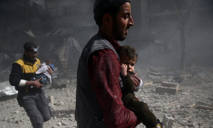 A man holds a child after an airstrike in the besieged town of Douma in eastern Ghouta in Damascus, Syria, Feb. 7, 2018. (Reuters/ Bassam Khabieh)