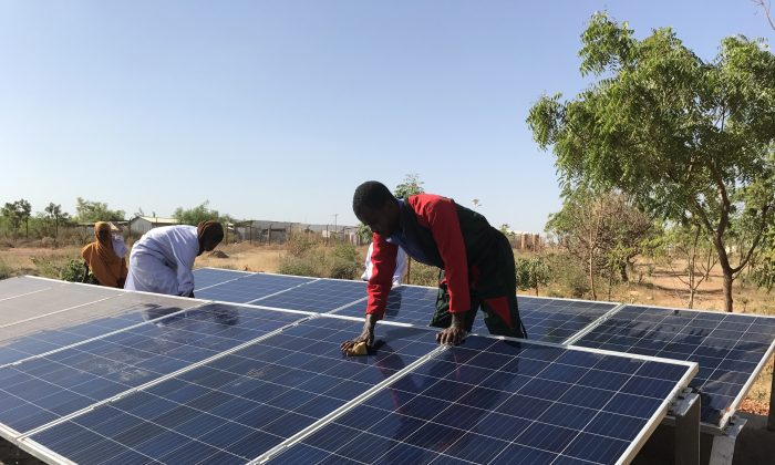 Adullahi Mohomed Adow carefully cleans dusty solar panels as routine maintenance in the hot and dusty climate of the Somali Region of Ethiopia. (Lisa Sim/Epoch Times)