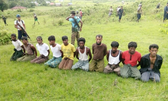 Ten Rohingya Muslim men with their hands bound kneel as members of the Myanmar security forces stand guard in Inn Din village Sept. 2, 2017. (Handout via Reuters)