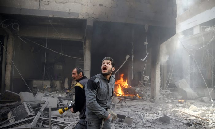 A Civil defence member reacts at a damaged site after an airstrike in the besieged town of Douma, Eastern Ghouta, Damascus, Syria Feb. 9, 2018. (Reuters/Bassam Khabieh)