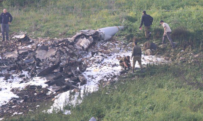 Israeli security forces walk next to the remains of an F-16 Israeli war plane near the Israeli village of Harduf, Israel Feb. 10, 2018. (Reuters/Herzie Shapira)