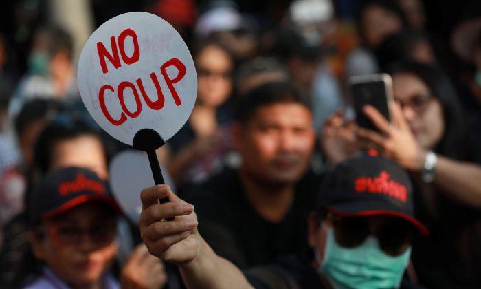 A Pro-democracy activist holds a fan during protest against junta near Democracy Monument in Bangkok, Thailand Feb. 10, 2018. (Reuters/Soe Zeya Tun)