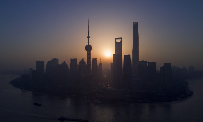 The sun rises behind the skyline of Shanghai in the Lujiazui Financial District, on Nov. 11, 2016. (Johannes Eisele/AFP/Getty Images)