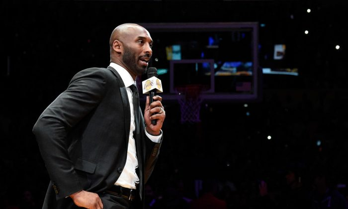 Kobe Bryant addresses the crowd at halftime as both his #8 and #24 Los Angeles Lakers jerseys are retired at Staples Center in Los Angeles, on Dec. 18, 2017. (Photo by Kevork Djansezian/Getty Images)