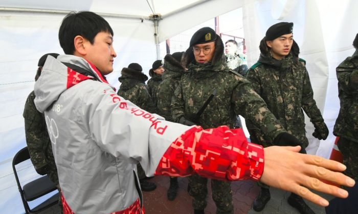 South Korean soldiers inspect a visitor at a security checkpoint as they replace security guards showing symptoms of the norovirus at the Gangneung Ice Arena in Gangneung ahead of the Pyeongchang 2018 Winter Olympic Games on Feb. 6, 2018. (Jung Yeon-Je/AFP/Getty Images)