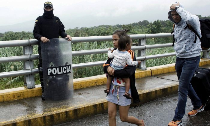 A woman carrying a child walks past a Colombian policeman after having crossed from Venezuela over the Simon Bolivar international bridge in Cucuta, Colombia February 13, 2018. (Reuters/Carlos Eduardo Ramirez)