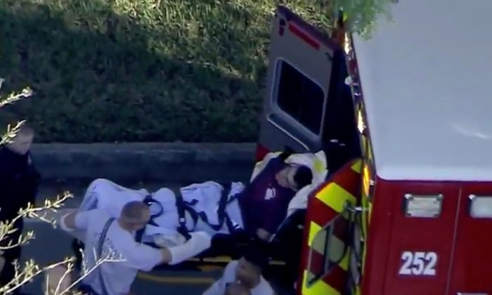 Nicolas de Jesus Cruz was placed in handcuffs by police is loaded into a paramedic vehicle after a shooting incident at Marjory Stoneman Douglas High School in Parkland, Florida, Feb. 14, 2018 in a still image from video. (WSVN.com via Reuters)