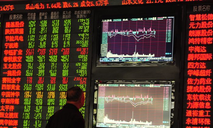 An investor observes a stock market display at an exchange hall in Fuyang City, Anhui Province of China, on March 29, 2016. (VCG/Getty Images)