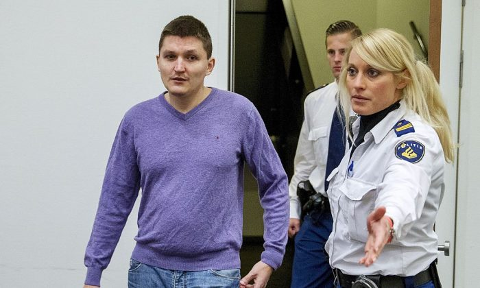 Vladimir Drinkman (L) is escorted by police officers at the courthouse in The Hague, on January 13, 2015. (Jerry Lampena/AFP/Getty Images)