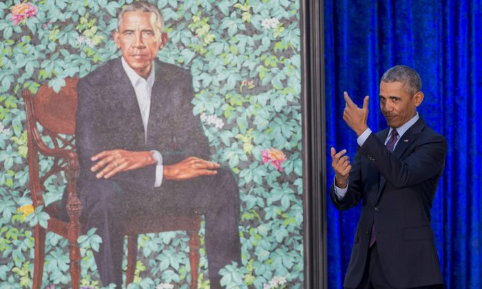 US President Barack Obama pretends to take a selfie as he looks at his by artist Kehinde Wiley after its unveiling at the Smithsonian's National Portrait Gallery in Washington, DC, February 12, 2018. (Photo credit should read SAUL LOEB/AFP/Getty Images)