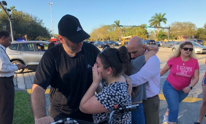 People react at Marjory Stoneman Douglas High School in Parkland, Fla., a city about 50 miles north of Miami on February 14, 2018 following a school shooting. (MICHELE EVE SANDBERG/AFP/Getty Images)