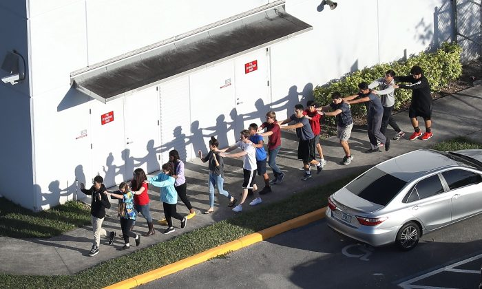 People are brought out of the Marjory Stoneman Douglas High School after a shooting at the school that left 17 people dead February 14, 2018 in Parkland, Florida. (Photo by Joe Raedle/Getty Images)