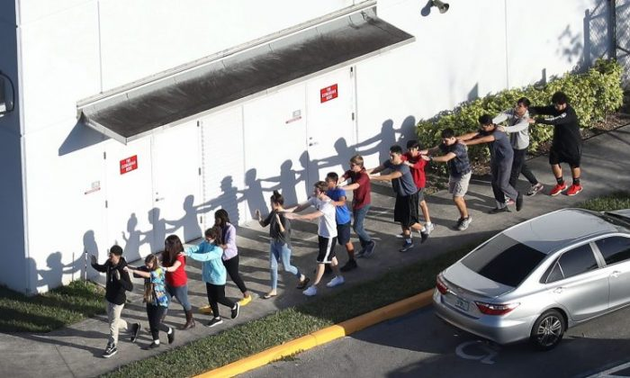 People are brought out of the Marjory Stoneman Douglas High School after a shooting at the school that left 17 people dead in Parkland, Florida, on Feb. 14, 2018. (Joe Raedle/Getty Images)