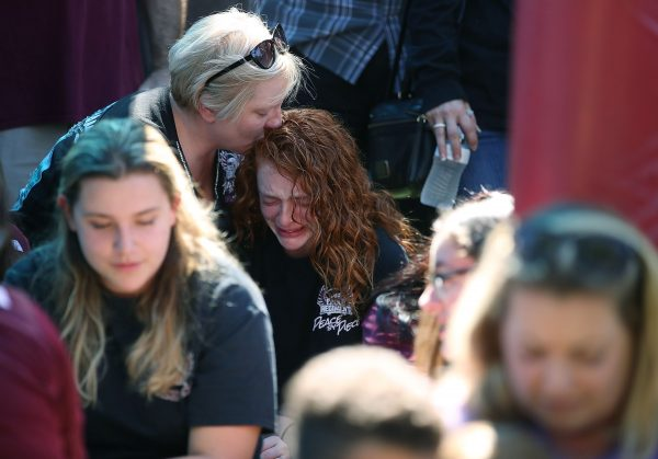 A student from the school where a mass shooting took place is comforted by her mother