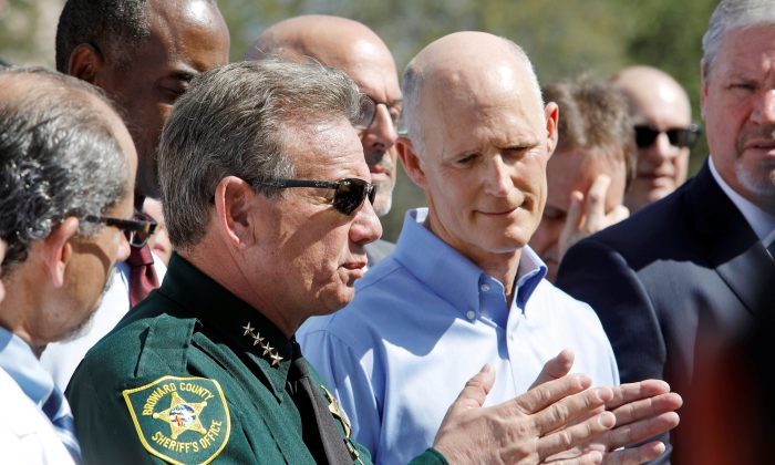 Broward County Sheriff Scott Israel speaks to the media while Florida Governor Rick Scott listens outside Marjory Stoneman Douglas High School one day after a shooting at the school left 17 dead, in Parkland, Florida on Feb. 15, 2018. (ReutersS/Jonathan Drake)