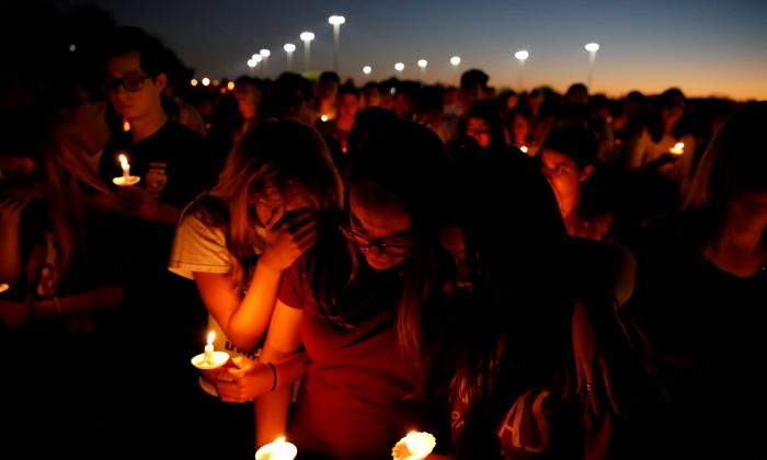 People attend a candlelight vigil for victims of yesterday's shooting at nearby Marjory Stoneman Douglas High School, in Parkland, Florida on Feb. 15, 2018. (Reuters/Carlos Garcia Rawlins)