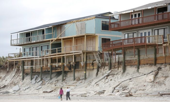 Beachgoers walk past condemned homes along heavily eroded shoreline at Vilando Beach, in the wake of Hurricane Irma and three nor'easters in the months since, north of St. Augustine, Florida, U.S., January 26, 2018. (Reuters/Gregg Newton)