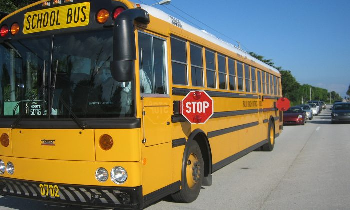 A school bus stops, preparing to unload students. (commons.wikimedia.org)