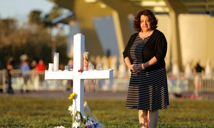 Diana Haneski, a librarian at Marjory Stoneman Douglas High School, poses for a portrait near one of the crosses erected for the victims of the school shooting in Parkland, Florida, U.S. February 16, 2018. (Reuters/Jonathan Drake)