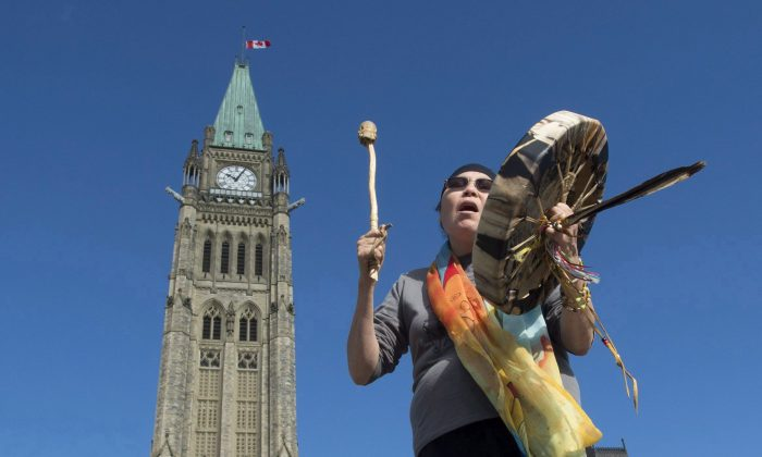 Chief Marcia Brown Martel sings outside the Parliament Buildings following a government news conference announcing a compensation package for Indigenous victims of the '60s Scoop on Oct. 6, 2017. (The Canadian Press/Adrian Wyld)