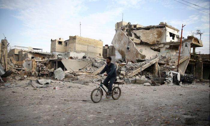 A young man rides bicycle near damaged houses in the besieged town of Douma, Eastern Ghouta, Damascus, Syria February 20, 2018. (Reuters/Bassam Khabieh)