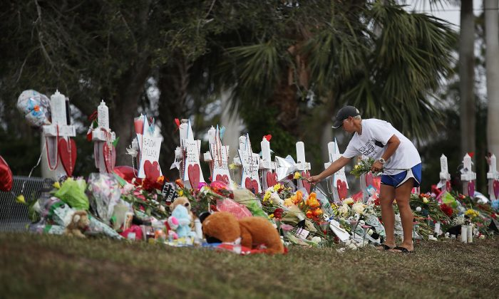 Melissa Shev visits a makeshift memorial setup in front of Marjory Stoneman Douglas High School in memory of the 17 people that were killed on Feb. 14, in Parkland, Florida on Feb. 20, 2018. (Joe Raedle/Getty Images)