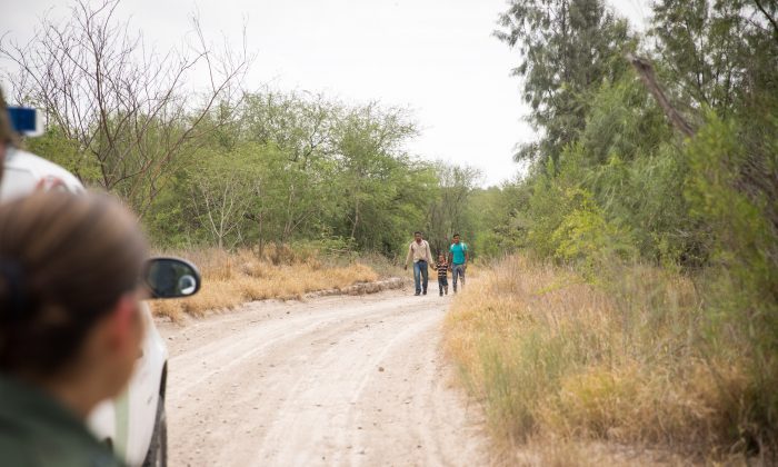 Two young men and a child approach a Border Patrol agent after crossing the Rio Grande from Mexico into the United States in Hidalgo County, Texas, on May 26, 2017.  (Benjamin Chasteen/The Epoch Times)