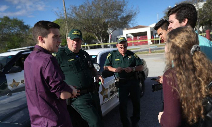 Cameron Kasky Jr., (L) and other students of Marjory Stoneman Douglas High School speak with Broward County Sheriff officers, Brad Griesinger and Jamie Rubenstein (L-R) who were guarding the front gate of the school on Feb. 18, 2018, in Parkland, Fla. Police arrested 19-year-old former student Nikolas Cruz for the mass shooting that killed 17 people on Feb 14, 2018. (Joe Raedle/Getty Images)