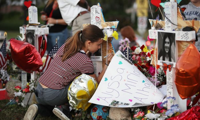 Victoria Seltzer, 11, writes a passage on a cross setup in a makeshift memorial in front of Marjory Stoneman Douglas High School in memory of the 17 people that were killed on February 14, on February 21, 2018 in Parkland, Florida. Police arrested 19-year-old former student Nikolas Cruz for killing 17 people at the high school. (Photo by Joe Raedle/Getty Images,)