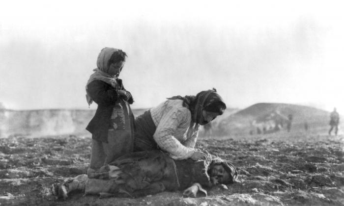 Armenian woman kneeling beside dead child in field. (American Committee for Relief in the Near East [Public domain], via Wikimedia Commons)