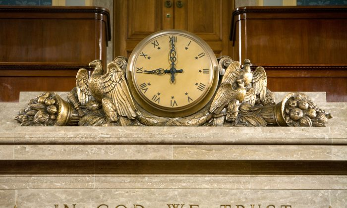 A clock and the motto 'In God We Trust' over the Speaker's rostrum in the U.S. House of Representatives chamber are seen Dec. 8, 2008, in Washington. (Brendan Hoffman/Getty Images)