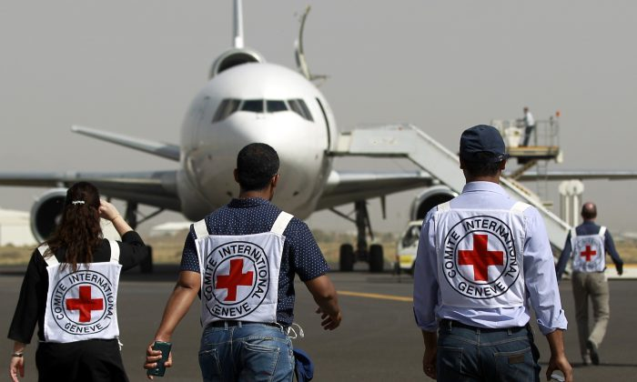 Members of the International Committee of the Red Cross walk toward a plane at the international airport in Sana'a, Yemen, on April 11, 2015. (Mohammed Huwais/AFP/Getty Images)