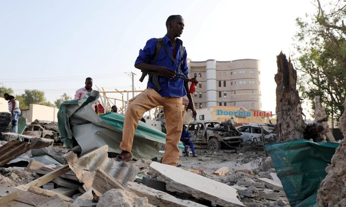 A security officer from Doorbin Hotel assesses the debris after a suicide car explosion in front of the hotel in Mogadishu, Somalia Feb. 24, 2018. (Reuters/Feisal Omar)