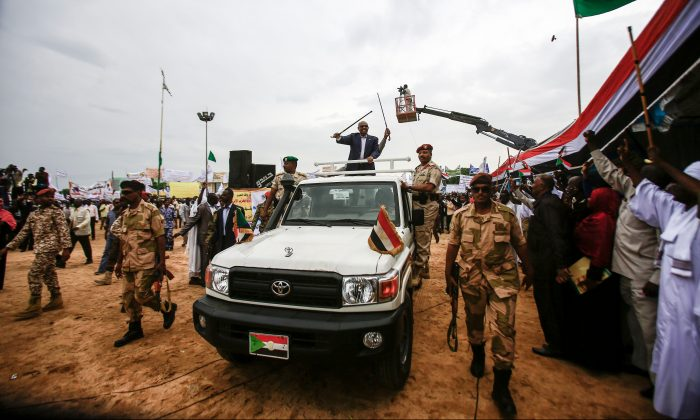 Sudanese President Omar al-Bashir (C) waves a walking stick as he rides in the back of a pickup truck in an advancing motorcade in Nyala, the capital of South Darfur province, on Sept. 21, 2017.