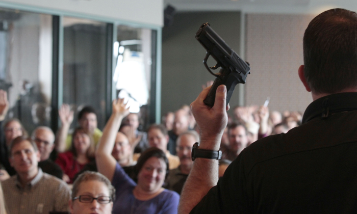 Firearm instructor Clark Aposhian holds a handgun up as he teaches a concealed-weapons training class to 200 Utah teachers on December 27, 2012 in West Valley City, Utah. (Photo by George Frey/Getty Images)