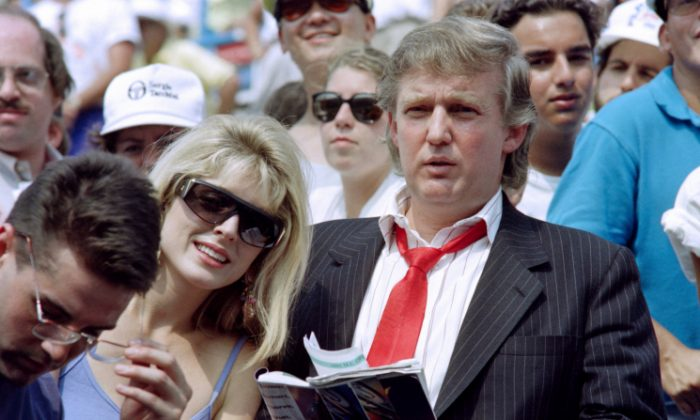 Donald Trump (R) and his fiancee Marla Maples watch second round action at the US Open tennis tournament on August 28, 1991.