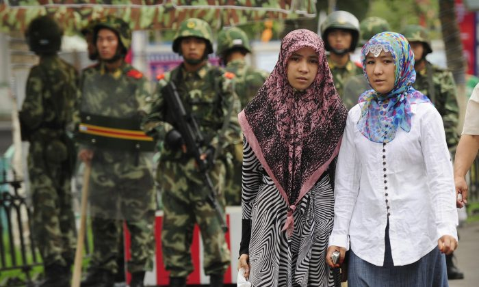 Two ethnic Uighur women pass Chinese paramilitary policemen standing guard outside the Grand Bazaar in Urumqi in China's Xinjiang region on July 14, 2009. (Peter Parks/AFP/Getty Images)