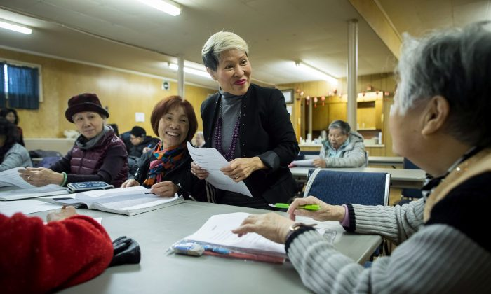 Amie Peacock (C) founder of the volunteer group Beyond the Conversation, speaks with senior citizens during a weekly group meeting in Vancouver on Feb. 23, 2018. (The Canadian Press/Darryl Dyck)