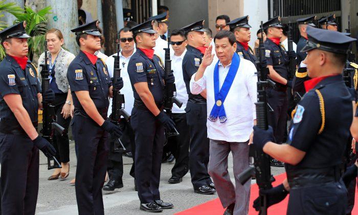 President Rodrigo Duterte salutes while passing members of custom police in Metro Manila, Philippines Feb. 6, 2018. (Reuters/Romeo Ranoco)