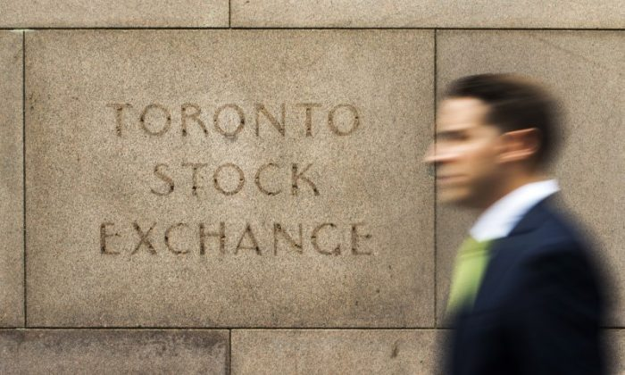 A man walks past a Toronto Stock Exchange (TSX) sign in Toronto on June 23, 2014. (Reuters/Mark Blinch)