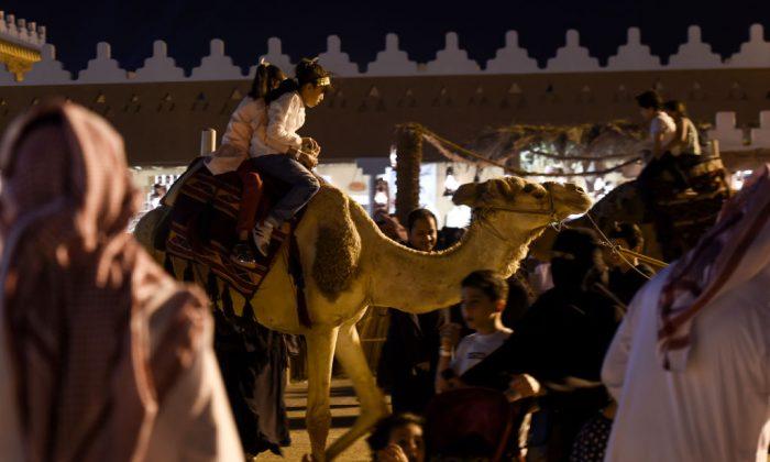 Saudi children ride a camel at Al-Qasim pavilion, during a cultural festival on the outskirts of the capital Riyadh in Saudi Arabia on Feb. 17, 2018. (Fayez Nureldine/AFP/Getty Images)