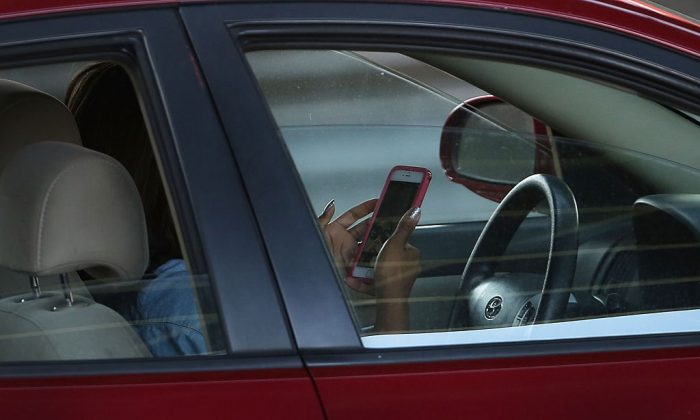 A driver uses a phone while behind the wheel of a car on April 30, 2016 in this file photo from New York City. (Photo by Spencer Platt/Getty Images)