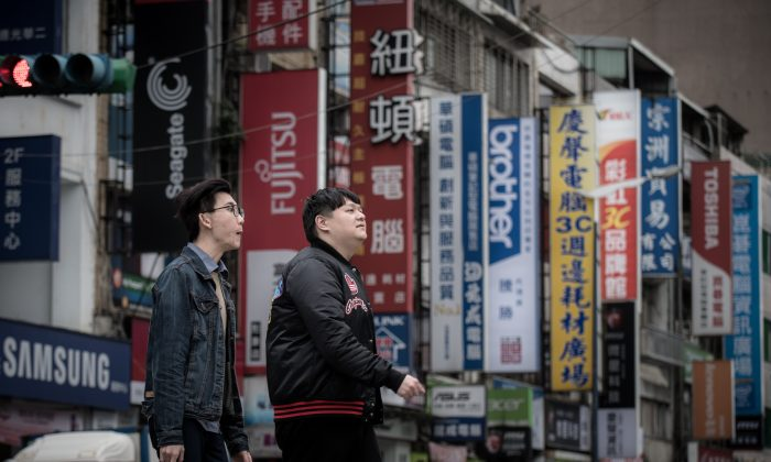 Pedestrians cross a street lined with the signs of electronic brands in Taipei on Jan. 12, 2016. China has announced a whopping list of new economic benefits designed to lure Taiwanese businesses and individuals to the mainland. (Philippe Lopez/AFP/Getty Images)