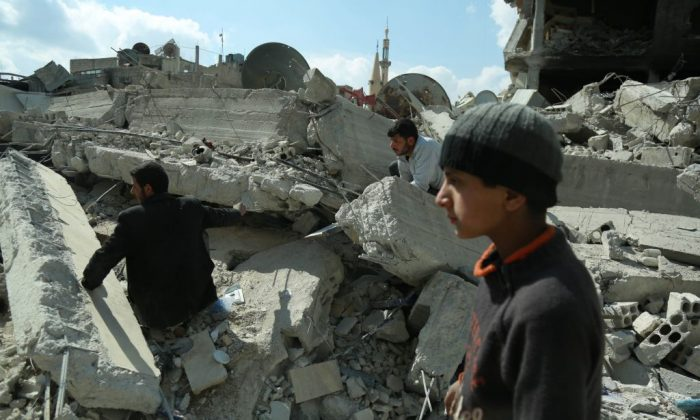Syrian civilians search for survivors amid the rubble of buildings which were destroyed earlier in regime air strikes, in the rebel-held besieged town of Douma in the eastern Ghouta region, on the outskirts of the capital Damascus, on Feb. 28, 2018. (Hamza Al-Ajweh/AFP/Getty Images)