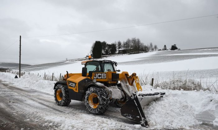 A JCB digger clears snow from the road between Delph and Denshaw in northern England on March 2, 2018.