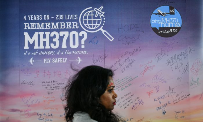 A woman walks past a banner bearing solidarity messages for passengers of the missing Malaysia Airlines flight MH370,  during a memorial event in Kuala Lumpur on March 3, 2018. (Manan Vatsyayana/AFP/Getty Images)