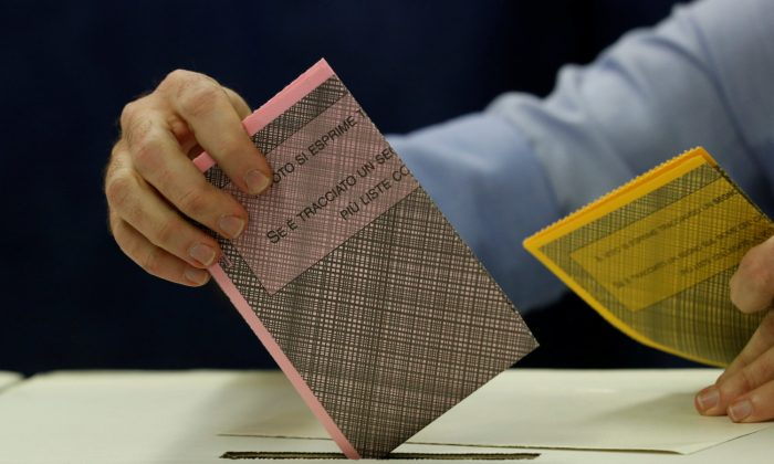 A man casts his vote at a polling station in Milan, Italy on Mar. 4, 2018. (REUTERS/Stefano Rellandini)
