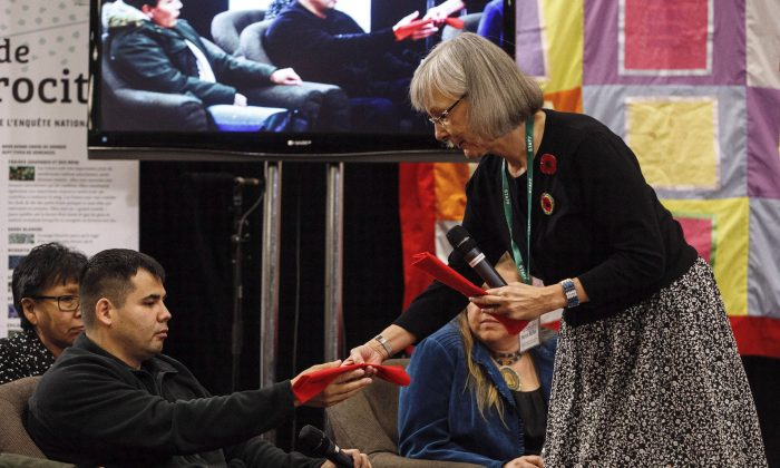 Chief Commissioner Marion Buller gives Paul Tuccaro an eagle feather after he gave testimony at the National Inquiry into Missing and Murdered Indigenous Women and Girls in Edmonton on Nov. 7, 2017. Tuccaro's sister Amber Tuccaro went missing in 2010. (The Canadian Press/Jason Franson)